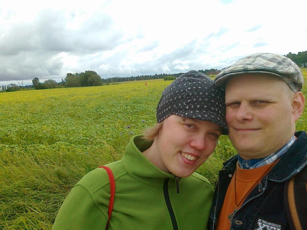 Kuvassa Tytti ja Anssi ohimot vastakkain, taustalla peltomaisema.