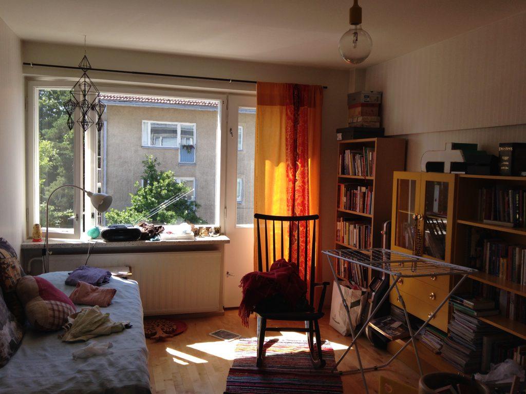 Kuvassa olohuone, takaseinällä ikkuna, josta tulee sisään valoa. Oikealla kirjahyllyt, vasemmalla vierasänky. Lattialla raidallinen matto, jonka päällä musta keinutuoli.