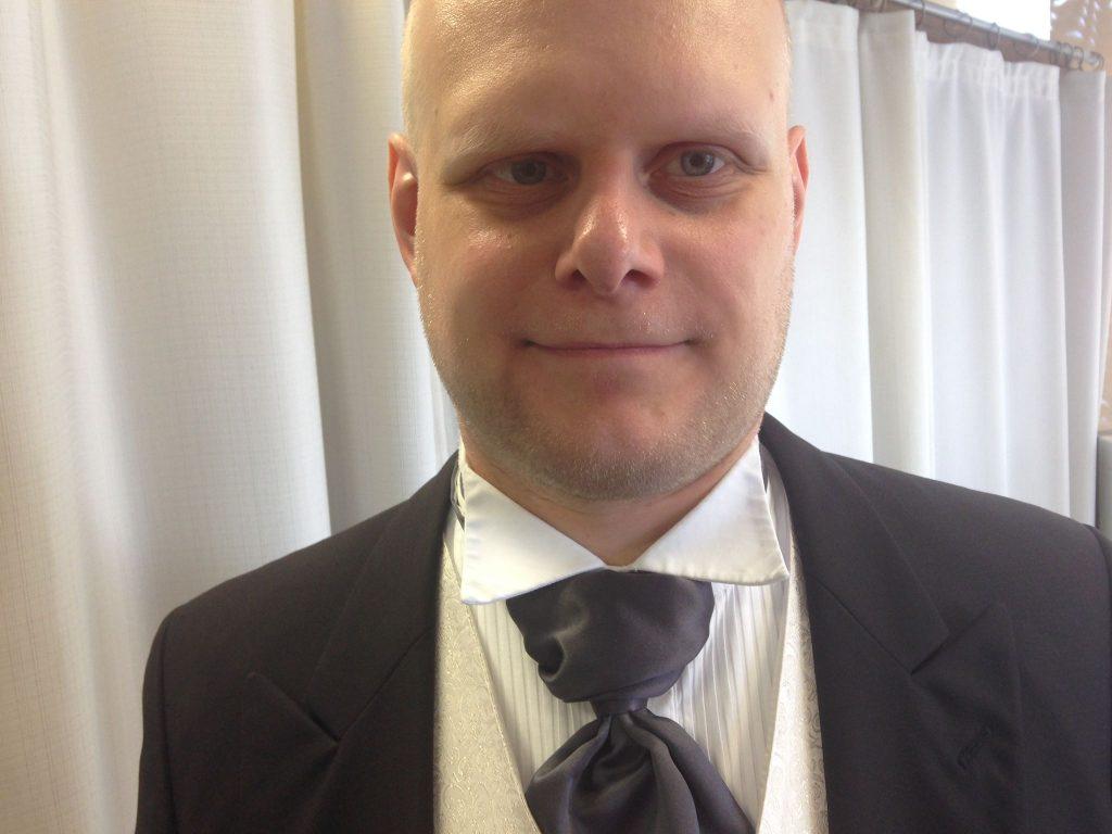 Kuvassa on Anssi, josta näkyy pää ja saketin takin yläosa, kauluspaita ja solmio.