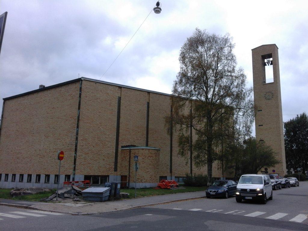 Kuvassa on Helsingin Meilahden kirkko Mannerheimintien suunnasta nähtynä. Keltatiilisessä kirkossa näkyy kirkkorakennus sekä kellotapuli.