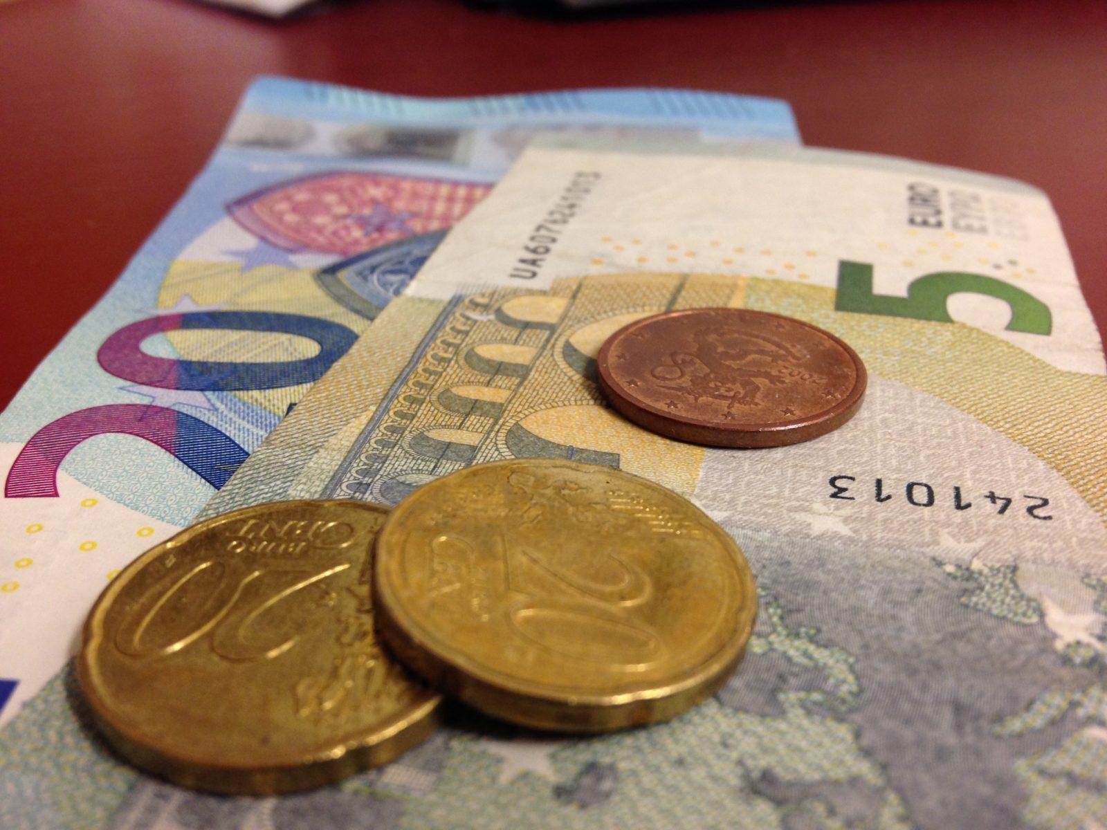Kuvassa 20 ja 5 euron setelit ja kolme kolikkoa niiden päällä.